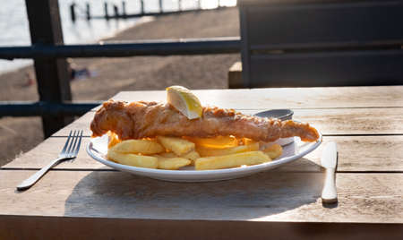 Fish and chips on plate at seaside outside, traditional favourite british food is battered cod or haddock served with fried potato chips