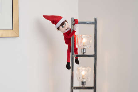 Elf on the shelf playing tricks hanging off light fitting. Cute tradition of sending Santas elf to check up on children just before christmas, but elves can be very naughty