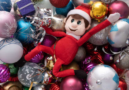 Elf on the shelf being naughty playing in a ball pond of christmas baubles. Cute tradition of sending Santas elf to check up on children just before christmas.