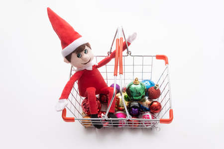Christmas shopping - Elf on the shelf being naughty sitting in a shopping basket of christmas baubles. Cute tradition of sending Santas elf to check up on children just before christmas.