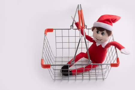 Christmas toy Elf in shopping basket, ready to go shopping for gifts