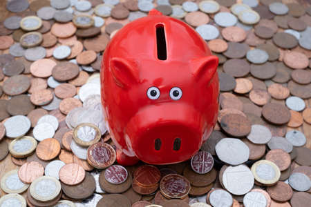 Piggy bank on background of uk coins, savings or budget concept