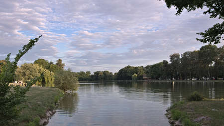 A beautiful park and a large pond with an islet in Nowa Huta, northern part of Krakow, invites to walking and bird watching Stock Photo