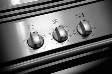 steel button: Oven knobs on metallic structure black and white Stock Photo
