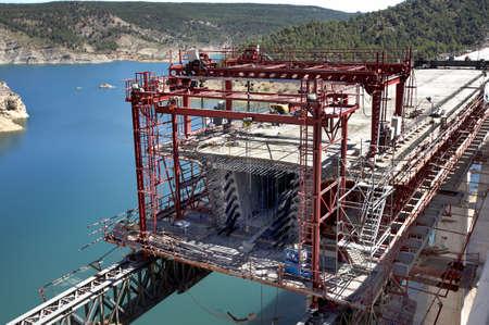 Railway bridge under construction on landscape blue sky and lake photo