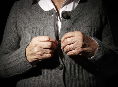 Old hands of an unrecognizable senior woman buttoning her self. 版權商用圖片