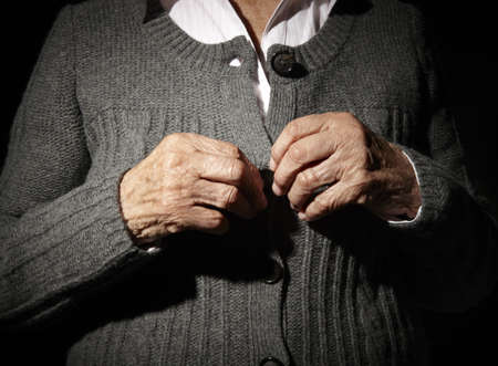 80 plus years: Old hands of an unrecognizable senior woman buttoning her self. Stock Photo