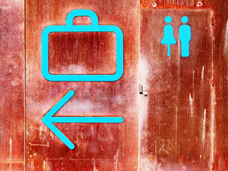 iron oxide: Baggage claim, arrow and rest room signs at sea port on iron oxide background