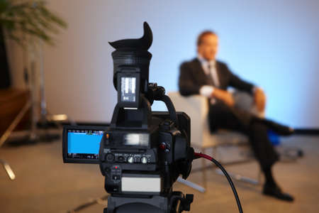 live action: Television interview program with selective focus on camera screen copy space