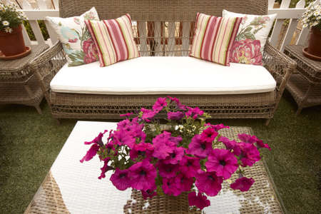 forniture: Exterior casa mobiliario de mimbre sostener objetos de decoraci�n con flores pieza central Foto de archivo