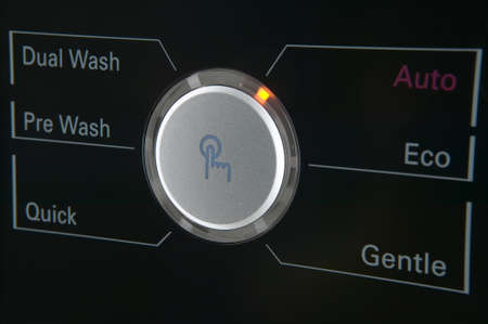 pannel: Close up of a modern washing machine control pannel button with timer and options low key against black background Stock Photo