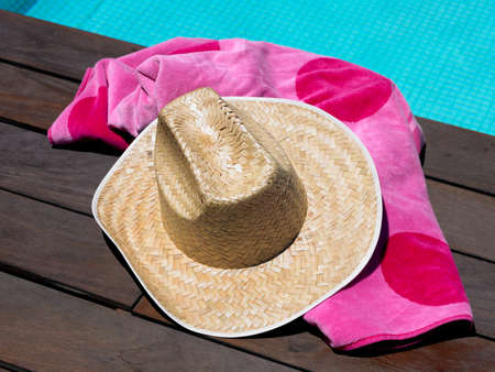 sun hat: Sun hat and beach towel by swimming pool.