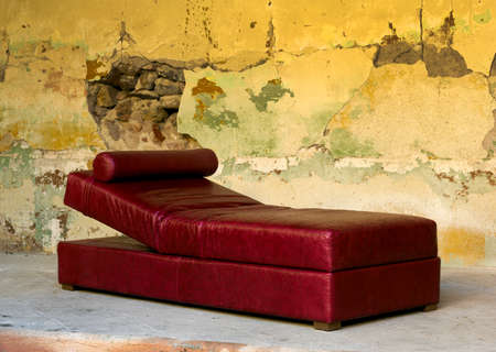 dilapidated wall: Red leather Chaise Longue against colorfull textured dilapidated wall