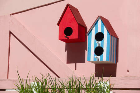 Man made bird houses on pink background Stock Photo