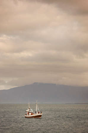 shrimp boat: Bay with fishing boat and mountains on cloudy day light vertical