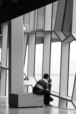 Facade detail of Harpa Concert Hall in Reykjavik with boy and girl looking outside vertical black and white