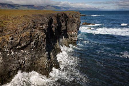 rock strata: The North Atlantic Ocean meets Island basaltic rocks coastline at Snaefellnes Peninsula Stock Photo