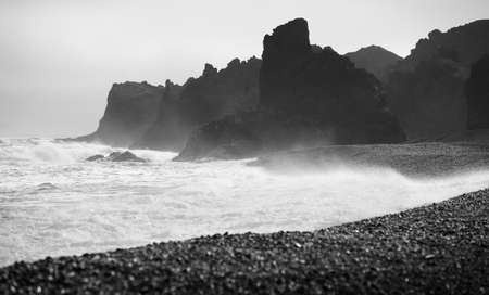 Sea coast volcanic rocks and black beach sand at Snaefellnes Peninsula Iceland black and white Stock Photo