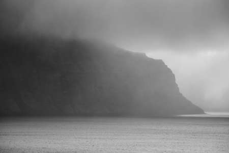 rock strata: Icelandic fiord with fog black and white Stock Photo