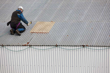 alluminum: Worker repairing an alluminum roof with insurance equipment Stock Photo