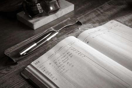 ledger: Antique wooden desk with ledger black and white image Stock Photo