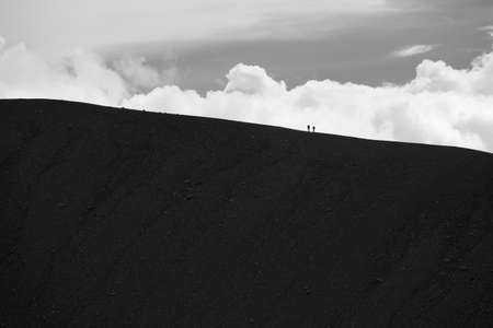 volcano slope: Silhouette of the mountain and two people at Hverfell extinct volcano slope in Myvatn Iceland