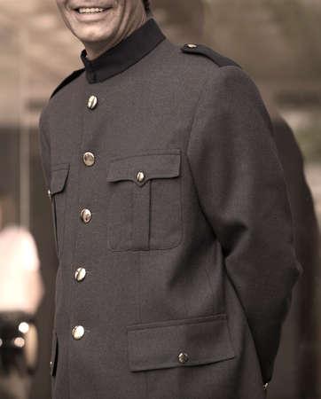 acomodador: Smiley Bellhop con botones dorados uniforme gris y Foto de archivo