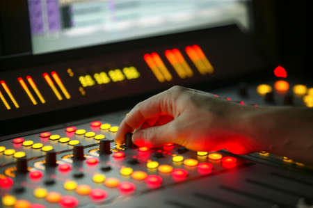 Male hand on control Fader on Film Mixing console Stock Photo - 25089685