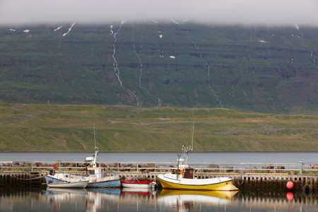 shrimp boat: Dock with fishing-trawlers in Seydisfjordur fjord under clodscape, Iceland