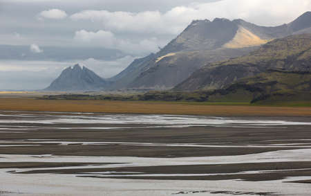 Plain formed of glacial sediments with water and sand at Lonsvik, Iceland East fjords Imagens