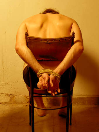 political prisoner: Man with tied hands vertical image warm tone Stock Photo