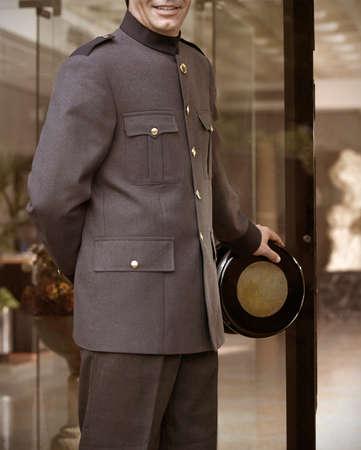 bellhop: Smiley Bellhop con uniforme gris de abrir la puerta del hotel