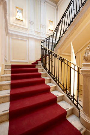Palace interior with red carpet on a marble stairway  Editorial