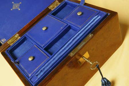 Abteile: Eine offene alte Schmuckschatulle mit F�chern auf blauem Samt