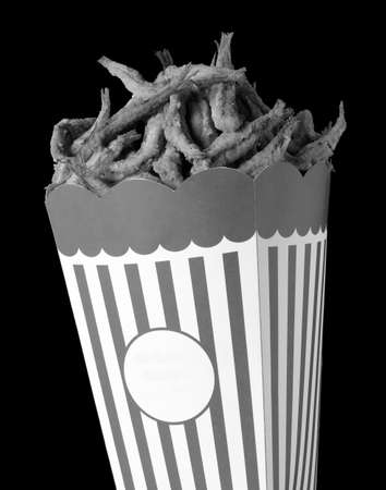 sarcastic: Ironic image of Cardboard Box with fried fish instead pop corn copy space black and white