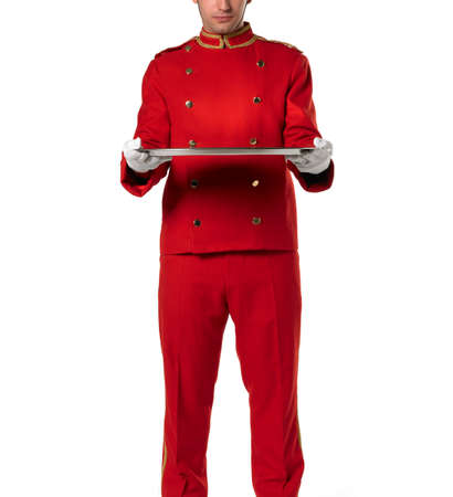 flexed: Bellhoper with red uniform bows presents a tray