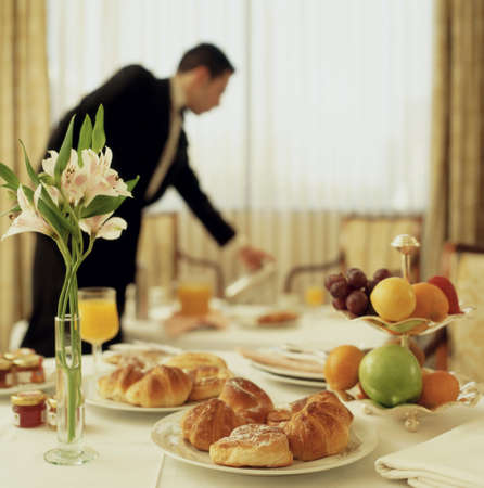 Big Hotel room service continental breakfast with waitress out of focus Stock Photo - 26127696