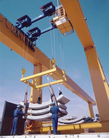 precast: Overhead travelling crane with workers and precast segments  Vertical  Editorial