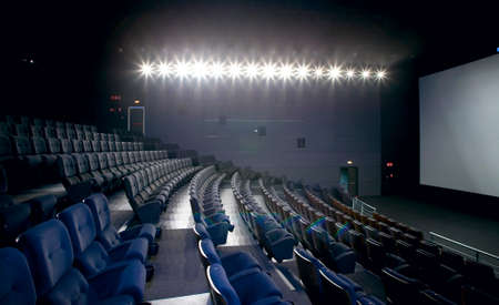 Cinema interior with lights on  Chairs and screen  Horizontal