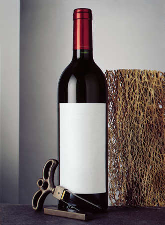 Still life with bottle of red wine and cork screw