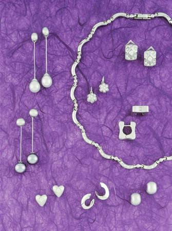 Collection of silver jewelry on purple background tone  Vertical photo