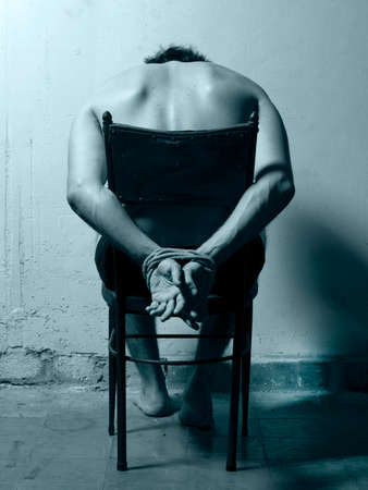 Tortured man in a chair with cold tones  Vertical Stock Photo - 28199655