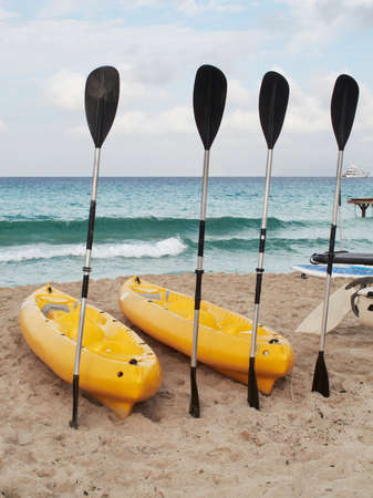 Paddles and kayaks on a mediterranean beach Horizontal