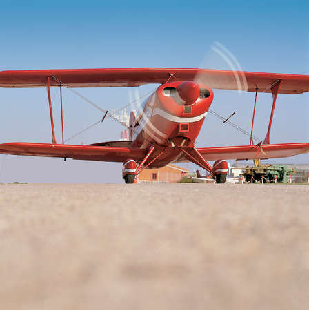 Red airplane ready to take off in an aerodrome photo