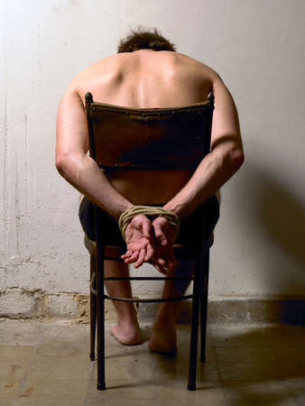 tortured: Tortured man on a chair with tied hands  Vertical