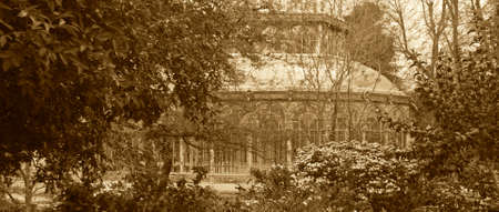 Vegetation in a park with antique metallic building in sepia tone photo