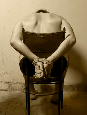tortured: Tortured man in a chair with tied hands  Sepia tone  Vertical format
