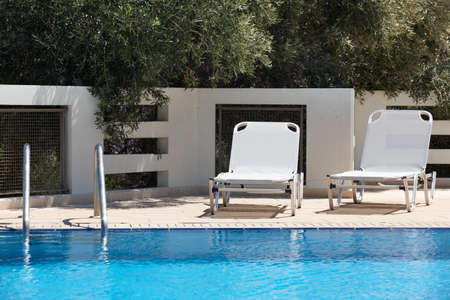 sunbeds: White sunbeds and swimming pool in summer.  Stock Photo