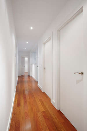 House corridor with white walls and wooden floor. Vertical format