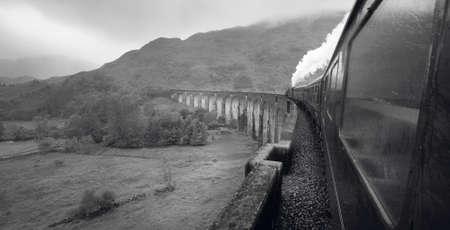 the jacobite: Scottish steam train passing a classic bridge. Horizontal Stock Photo
